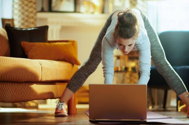 Junge Sportlerin arbeitet am Laptop, während sie Übungen machen – Foto