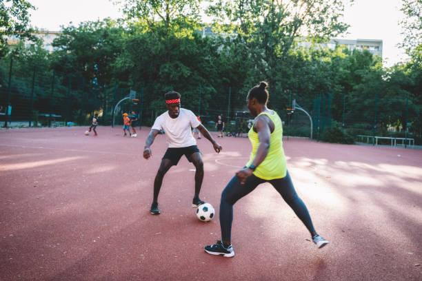 junger Sportler und junge Sportler, die auf dem Hartplatz Fußball spielen – Foto