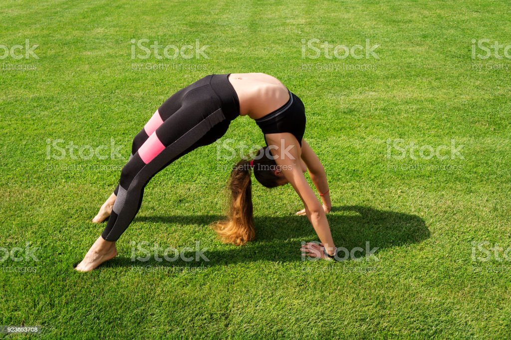 Young sportsman doing sports exercises on the grass stock photo