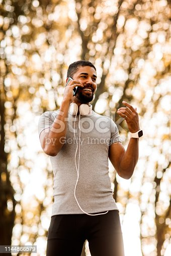 istock Young sportsman having a conversation on a mobile phone outdoors 1144866579