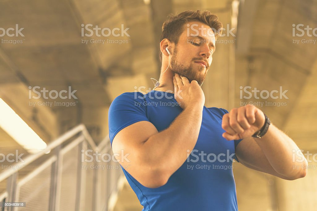 Young sportsman measuring pulse and heart rate during workout. stock photo
