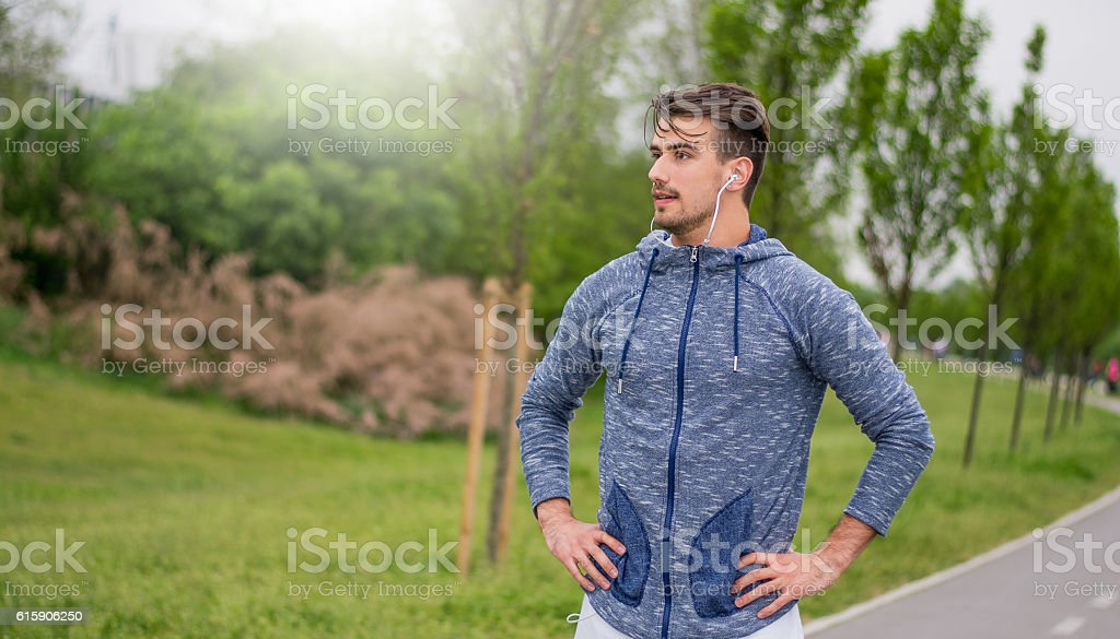 Young sportsman resting after a long run stock photo