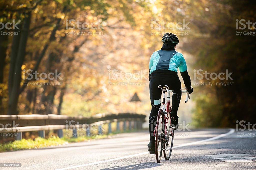 Young sportsman riding bicycle outside in sunny autumn nature - Foto de stock de Accesorio de cabeza libre de derechos
