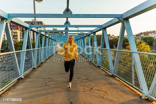 Young Strong Athlete in Yellow Hoodie Jogging Outdoors At the Bridge And Listening To Music with Headphones, Male Runner Working Out on the City Bridge. Sportsman Do Physical Exercises