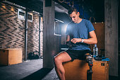 Young sportsman with a leg disability putting on his training gloves while preparing for a training session on a wooden gym box in a cross fit area of a gym