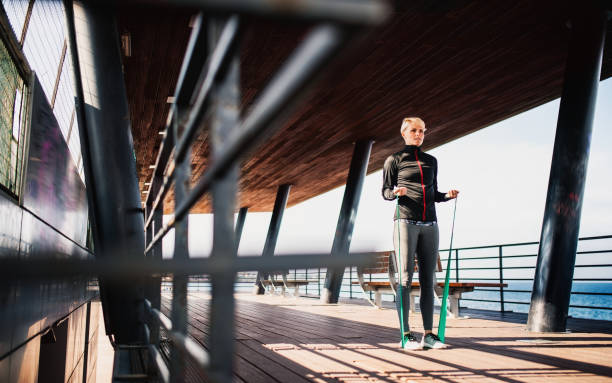 a young sportswoman doing exercise by sea. - resilience concept stock photos and pictures