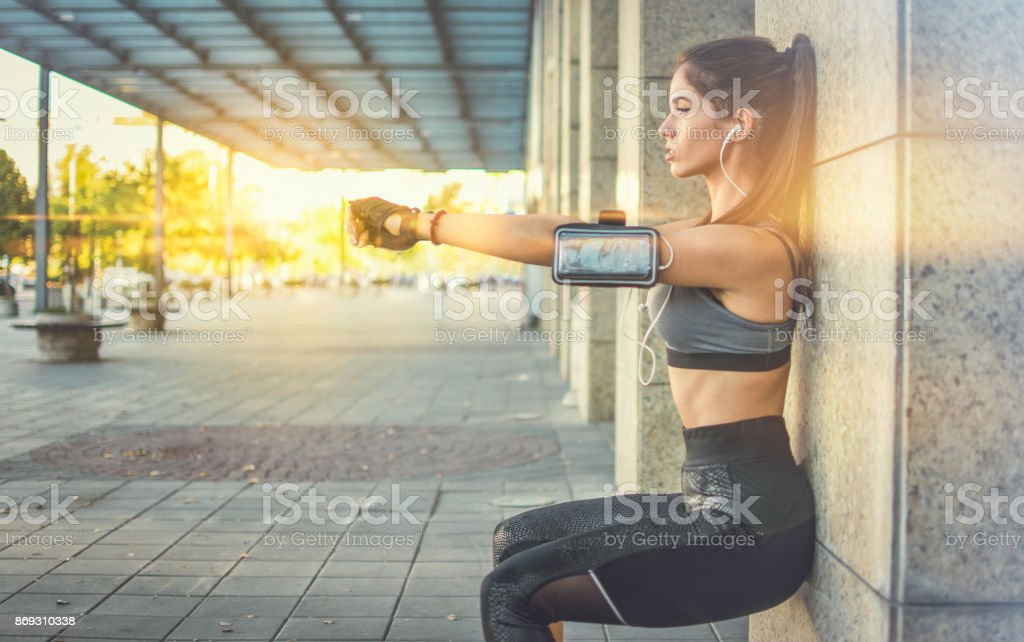 Young sportswoman doing squats against wall outdoors. stock photo