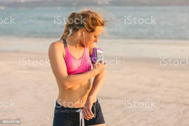 Młoda Sportsmenka W Słuchawkach Za Pomocą Smartfona W Obudowie Z Opaską Na Plaży Z Morzem Za - zdjęcia stockowe i więcej obrazów Aktywny tryb życia