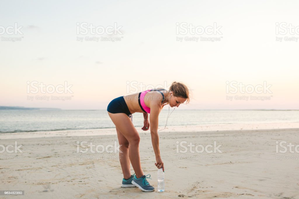 young sportswoman in earphones with smartphone in armband case picking up bottle of water on beach with sea behind - Zbiór zdjęć royalty-free (Aktywny tryb życia)