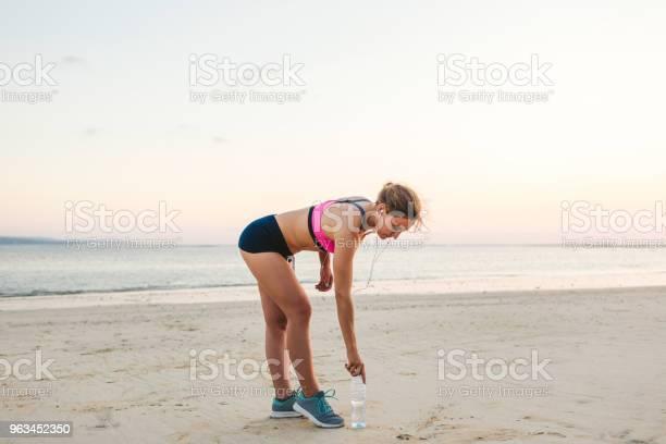 Młoda Sportsmenka W Słuchawkach Ze Smartfonem W Obudowie Opaski Zbierająca Butelkę Wody Na Plaży Z Morzem Za - zdjęcia stockowe i więcej obrazów Aktywny tryb życia