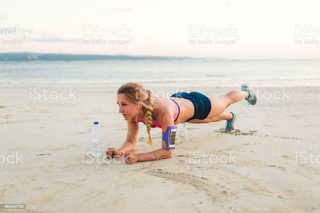 unga idrottskvinna i hörlurar med smartphone i kör Armbandsväska case och flaska vatten gör plankan på sandstrand - Royaltyfri Aktiv livsstil Bildbanksbilder