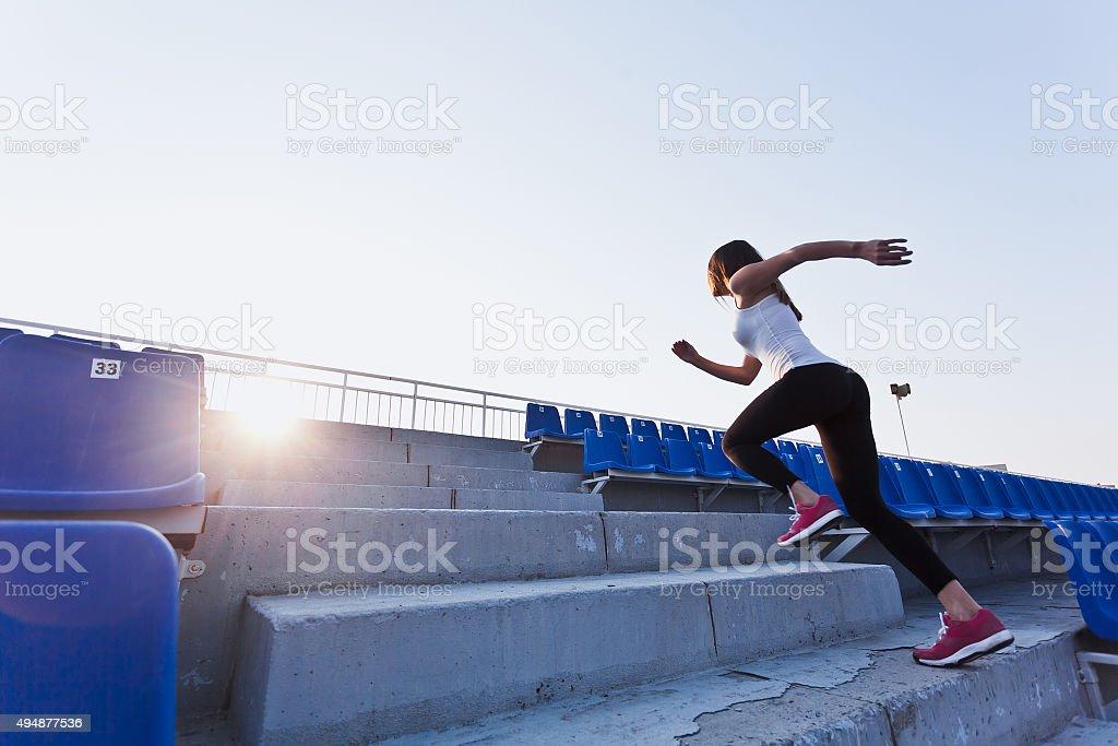 Young sportswoman in sportswear running upstairs on stadium during training stock photo