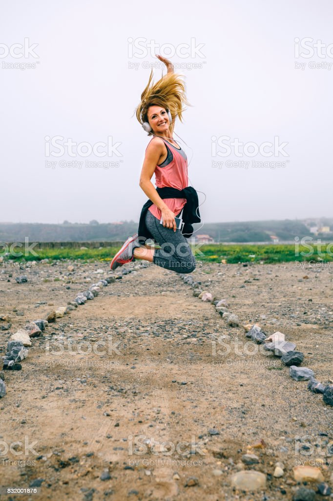Young sportswoman jumping on the road stock photo