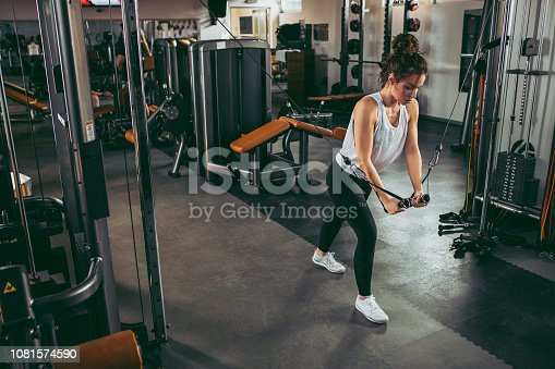 619088796 istock photo Young sportswoman lifting weights in gym 1081574590