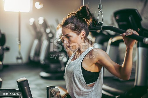 619088796 istock photo Young sportswoman lifting weights in gym 1081574746