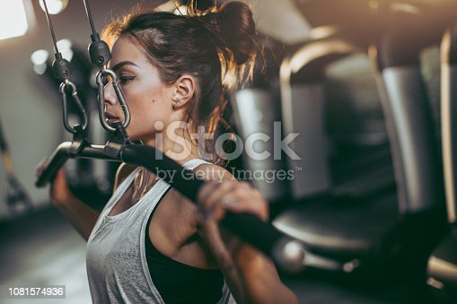 619088796 istock photo Young sportswoman lifting weights in gym 1081574936