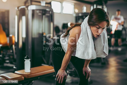 619088796 istock photo Young sportswoman lifting weights in gym 1081576450