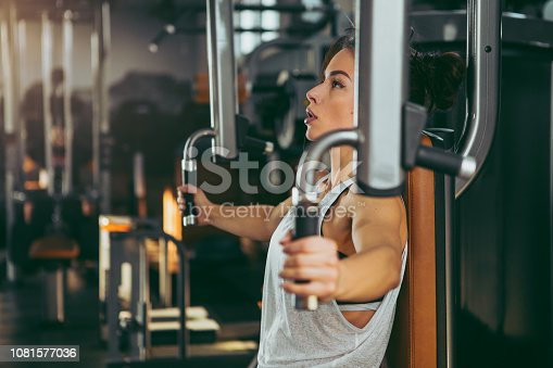 619088796 istock photo Young sportswoman lifting weights in gym 1081577036