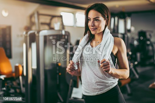 619088796 istock photo Young sportswoman lifting weights in gym 1081577348