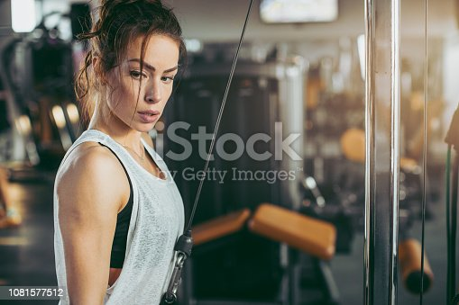 619088796 istock photo Young sportswoman lifting weights in gym 1081577512