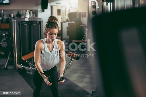 619088796 istock photo Young sportswoman lifting weights in gym 1081577822