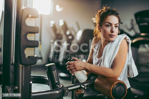 619088796 istock photo Young sportswoman lifting weights in gym 1081578058