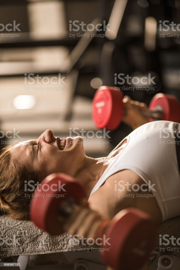 Athletic woman making an effort while exercising with heavy hand...