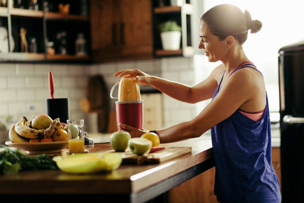 Young sportswoman making healthy smoothie in the kitchen. stock photo