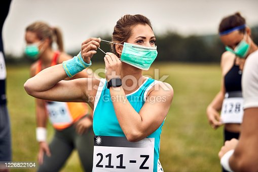 Athletic woman putting on face mask while participating in marathon race in nature.