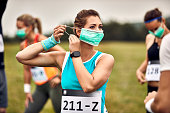 istock Young sportswoman putting on protective face mask while preparing for a marathon. 1226822104