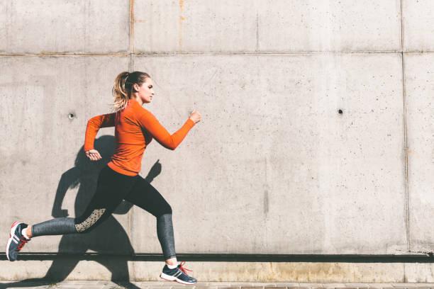 junge Sportlerin läuft vor Betonwand – Foto