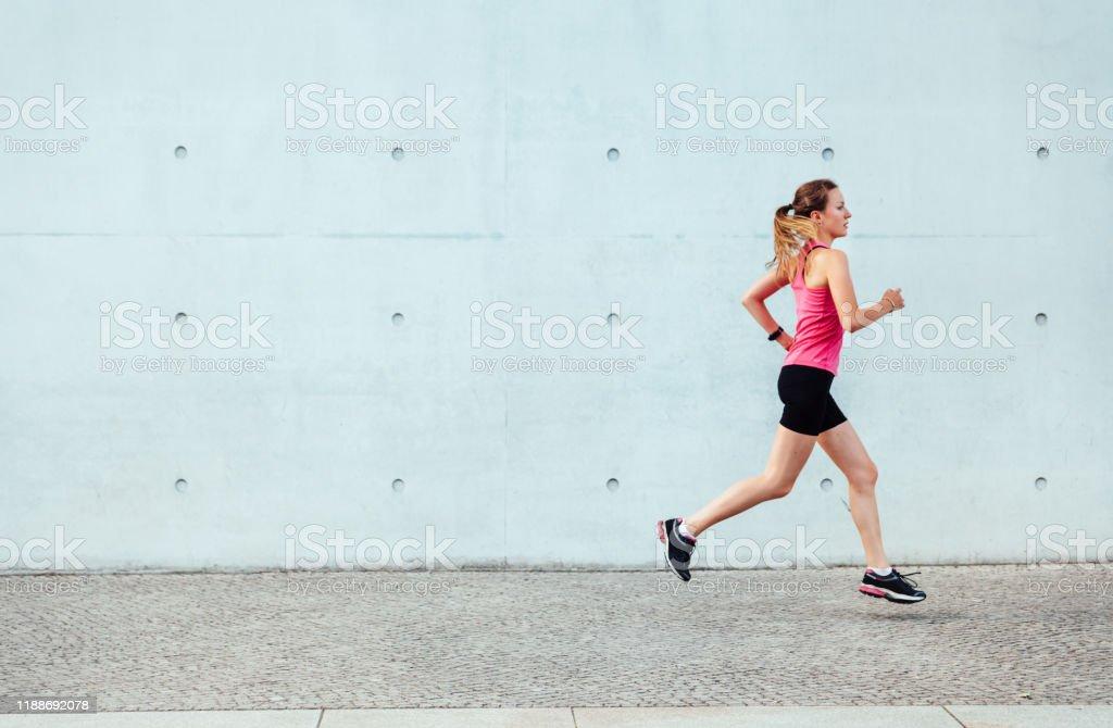 junge Sportlerin läuft vor Betonwand - Lizenzfrei 20-24 Jahre Stock-Foto