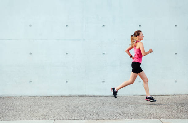 young sportswoman running in front of concrete wall stock photo
