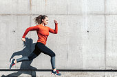 young sportswoman in red sports dress running outdoors in front of concrete wall