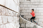 young sportswoman in red sports dress running up old stone stairs outdoors in town