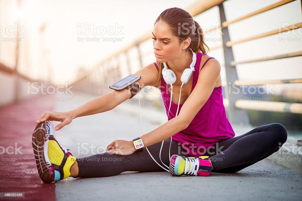 sportswoman joven de estiramiento después de una sesión de ejercicios con equipos cardiovasculares - foto de stock