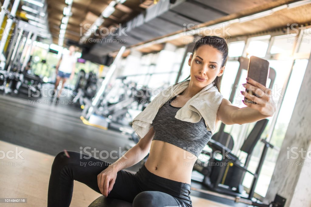 Young sportswoman taking selfie after sports training in gym stock photo