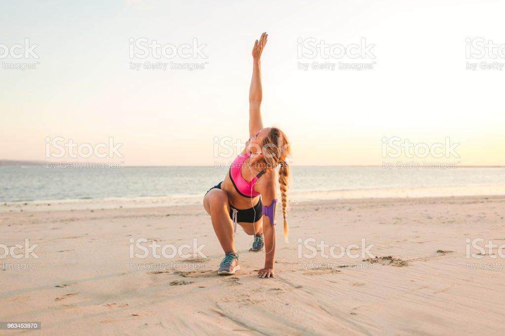 Junge Sportlerin mit Smartphone bei der laufenden Armbinde Fall Ausübung am Strand mit Meer hinter - Lizenzfrei Aktiver Lebensstil Stock-Foto