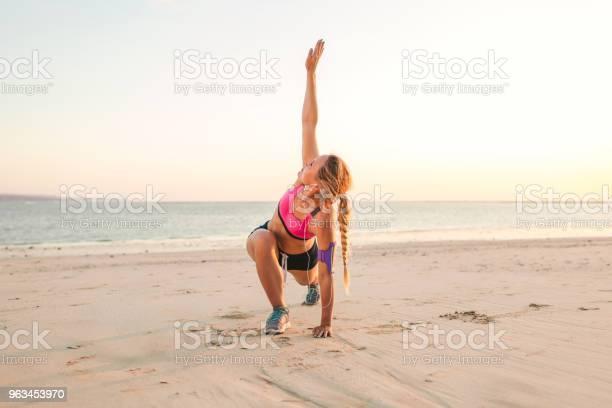 Junge Sportlerin Mit Smartphone Bei Der Laufenden Armbinde Fall Ausübung Am Strand Mit Meer Hinter Stockfoto und mehr Bilder von Aktiver Lebensstil
