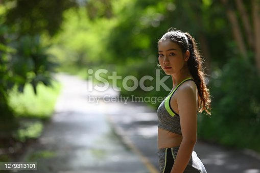 Young sportswoman young fitness woman runner standing in the park.