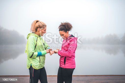 Shot of two young sportswomen checking pulse on smart watch. They are standing next to a lake and are smiling. Fog is above the lake.