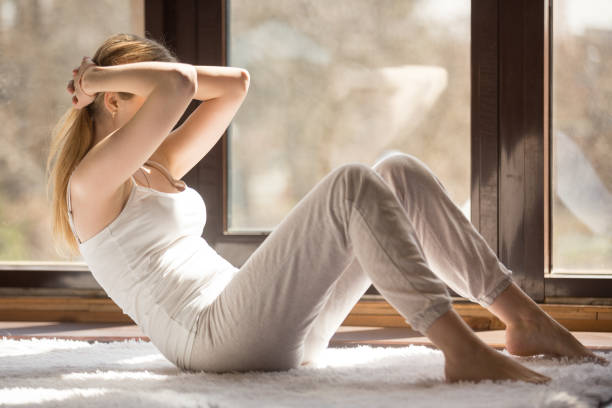 young sporty attractive woman doing rock press exercise at home - peso mosca foto e immagini stock
