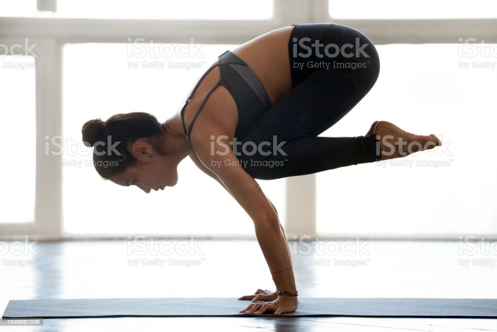 Young sporty attractive woman practicing yoga, doing Crane exercise stock photo