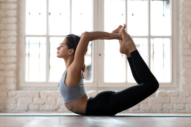 Young sporty attractive woman practicing yoga, doing Dhanurasana exercise stock photo