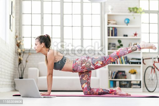 Young sporty attractive woman practicing yoga, doing Donkey Kick exercise in front of her laptop