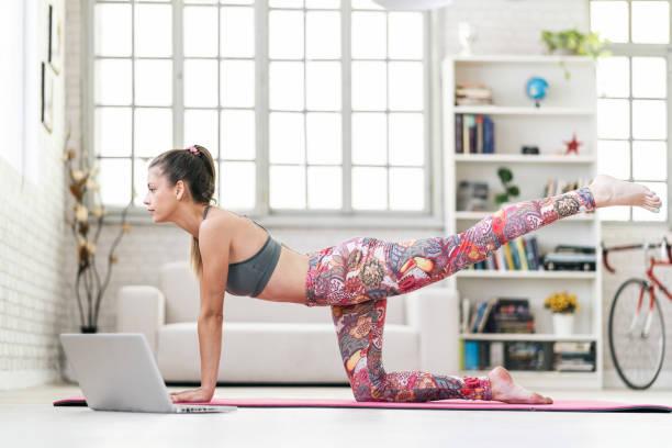 Junge sportlich attraktive Frau, die Yoga praktiziert, macht Donkey Kick-Übung vor ihrem Laptop – Foto