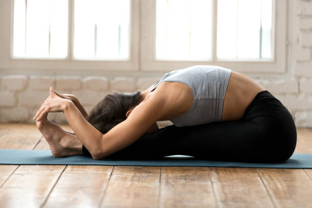 Young sporty attractive woman practicing yoga, doing paschimottanasana exercise Young sporty attractive woman practicing yoga, doing paschimottanasana exercise, Seated forward bend pose, working out, wearing sportswear, black pants and top, indoor full length, white yoga studio bending stock pictures, royalty-free photos & images