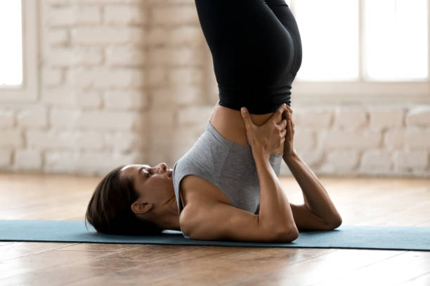 Young sporty attractive woman practicing yoga, doing Salamba Sarvangasana exercise Young sporty attractive woman practicing yoga, doing Salamba Sarvangasana exercise, supported Shoulder stand pose, working out, wearing sportswear, pants and top, indoor close up, white yoga studio shoulder stand stock pictures, royalty-free photos & images