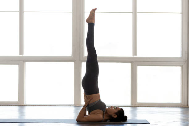 Young sporty attractive woman practicing yoga, doing supported Shoulder stand Young sporty attractive woman practicing yoga, doing Salamba Sarvangasana exercise, supported Shoulder stand pose, working out, wearing sportswear, grey pants, top, indoor full length, at yoga studio shoulder stand stock pictures, royalty-free photos & images