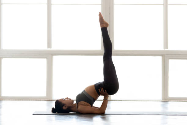 Young sporty attractive woman practicing yoga, doing Viparita Karani exercise Young sporty attractive woman practicing yoga, doing Viparita Karani exercise, upside-down pose, working out, wearing sportswear, grey pants, top, indoor full length, at yoga studio shoulder stand stock pictures, royalty-free photos & images